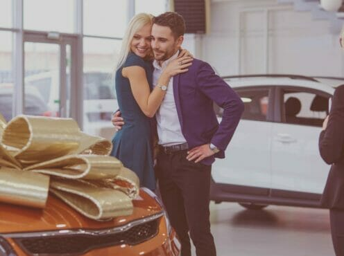 a man surprises his wife with a new car topped with a bow at the dealership