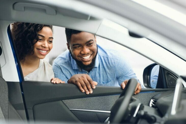 a happy couple looking inside the driver's side window of a car at the dealership