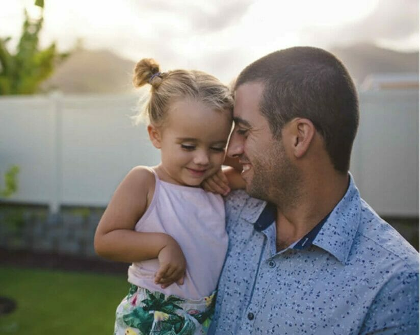dad holding daughter while standing in backyard
