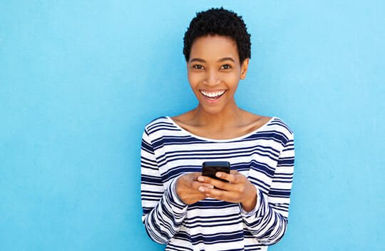 woman holding phone standing against blue background