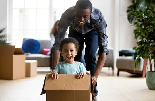 child in box being pushed across floor by dad