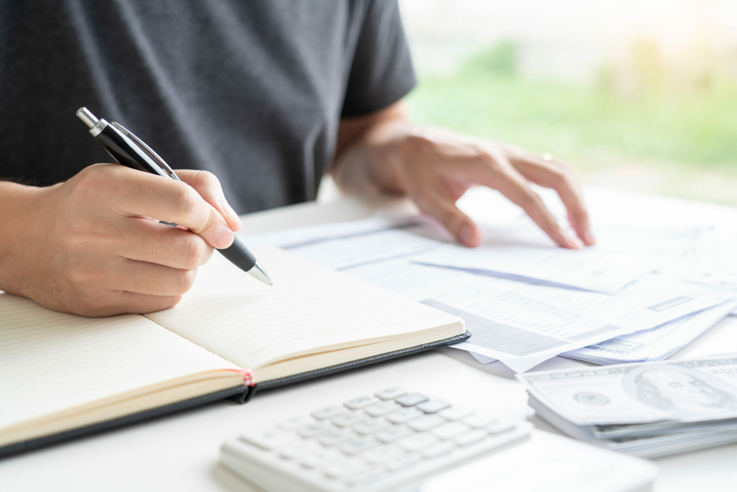 man with checkbook and calculator estimating how much to keep in checking account