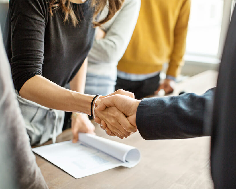 woman and man shaking hands over document