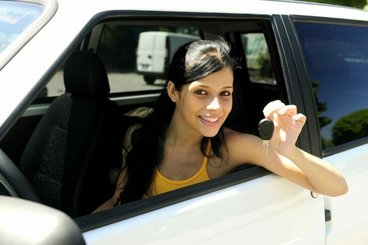 a first time car buyer smiling in the driver's seat with keys to her new car in hand