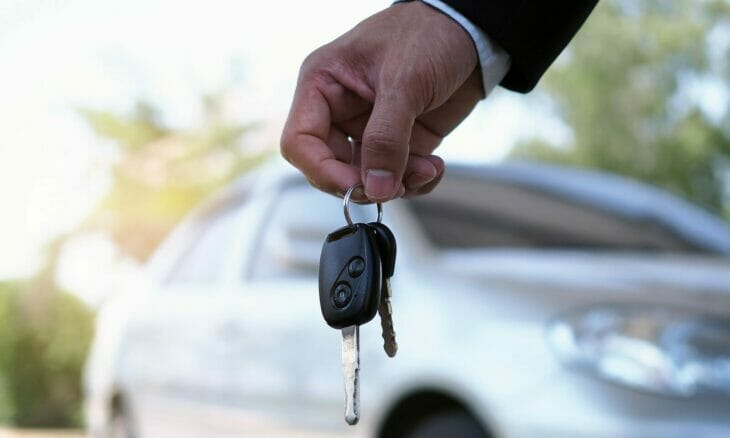 a man's hand holding car keys next to his new vehicle
