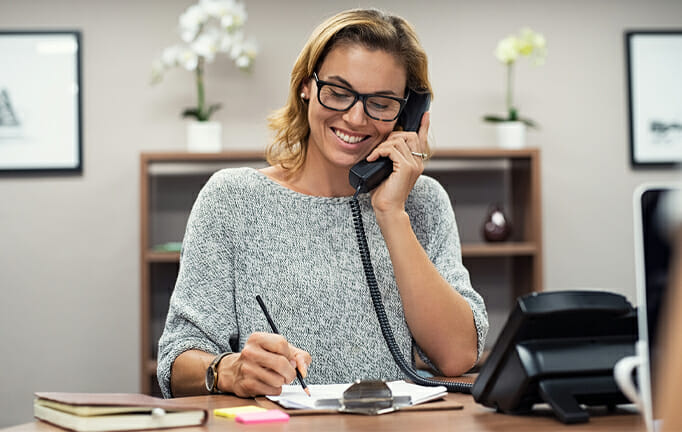 smiling woman on phone taking notes