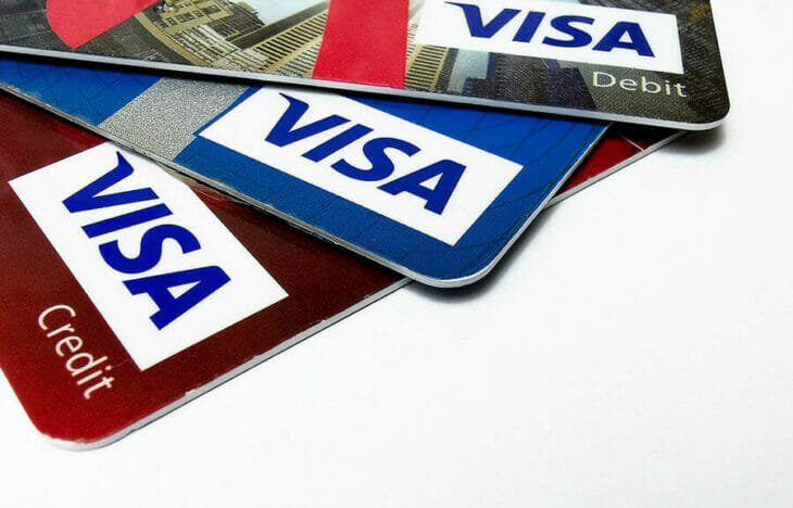 a stack of three Visa credit and debit cards - compressed
