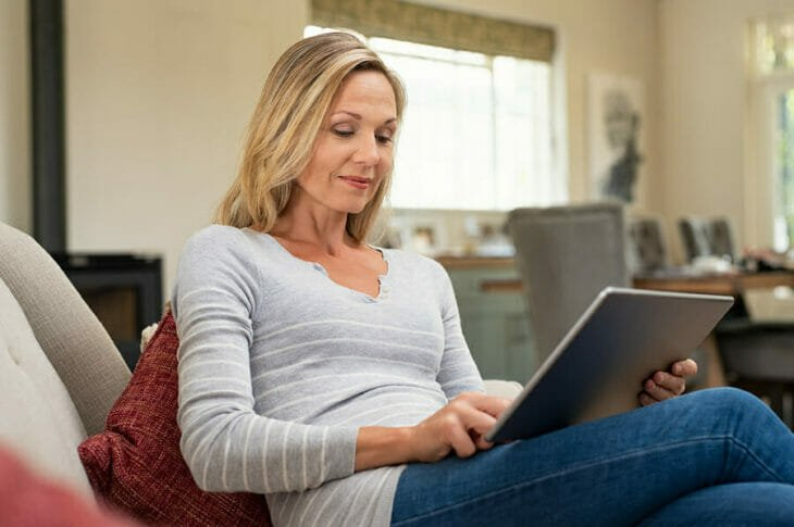 woman experiences the benefits of a checking account by accessing her finances on a tablet
